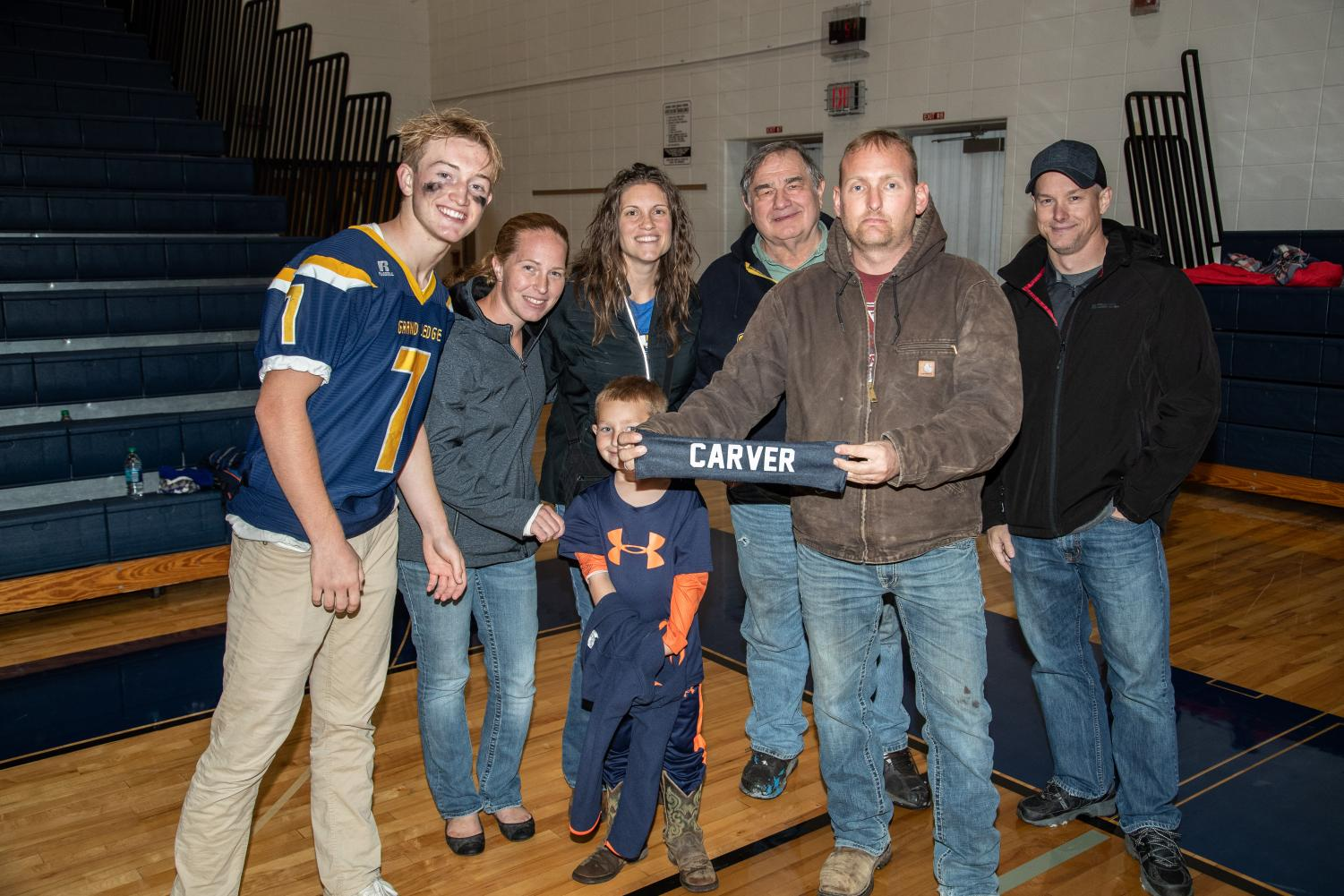 Grand Ledge Senior linebacker, Bear Nelson, taking a photo with the family of one of our fallen heroes.