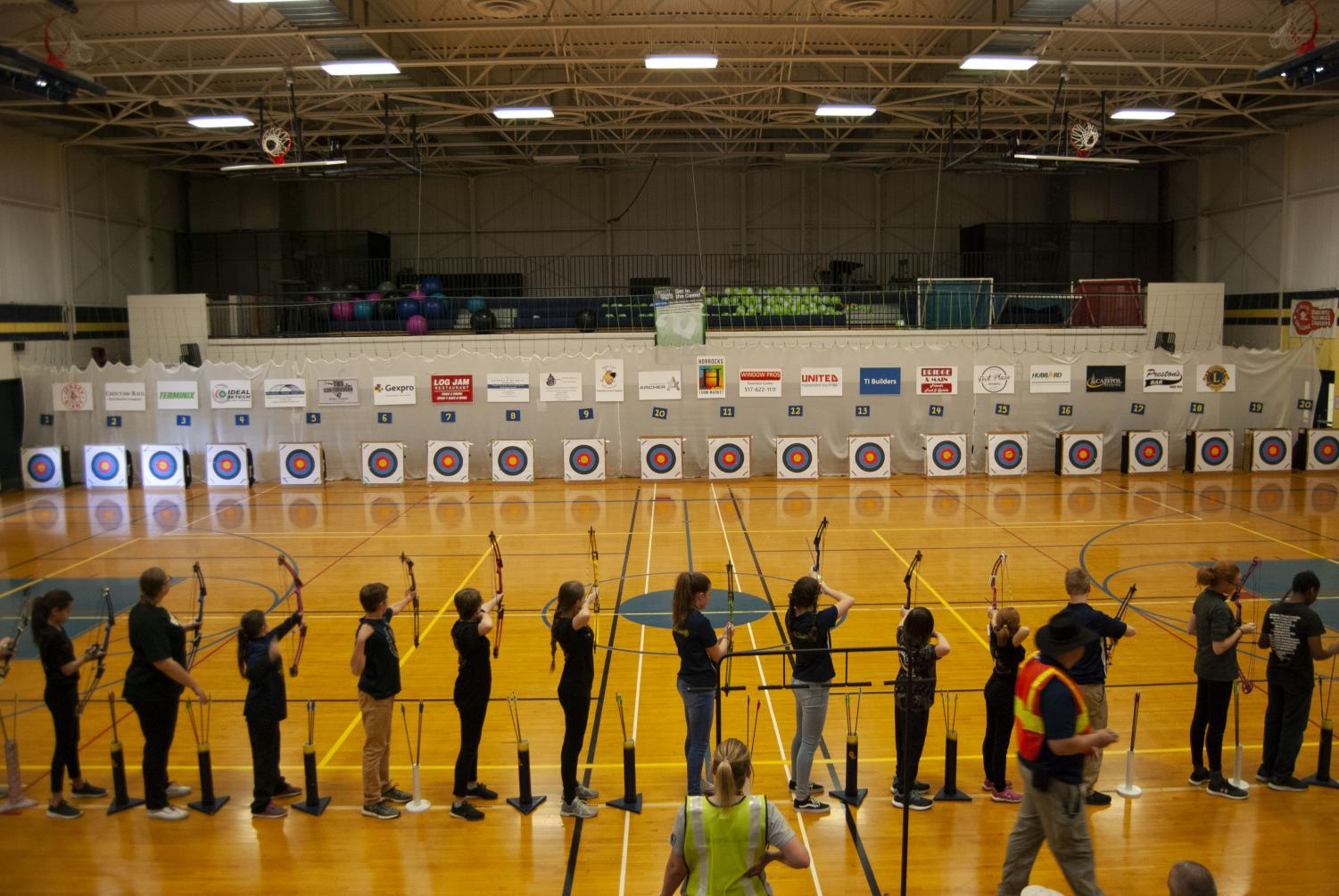 Archers shoot from the 15 meter line at the Grand Ledge Archery Classic. Volunteers helped with setting up the targets, sponsor signs, target numbers, and even put the shooters tape down on the floor.