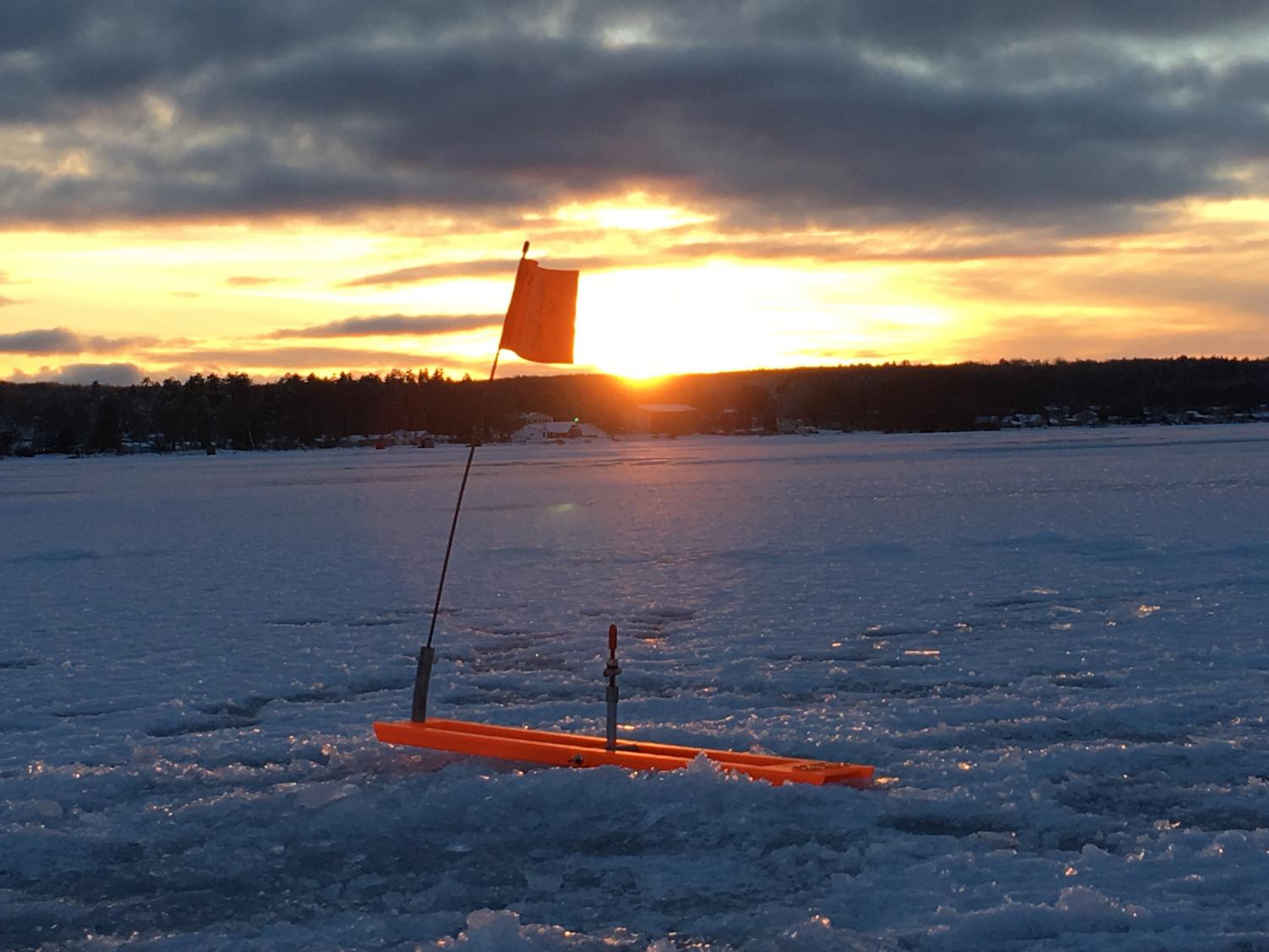 The sun sets on the horizon of Houghton Lake on Jan. 1, while another fish trips the flag on a tip-up. The cold temperatures thickened the ice to around 10 inches for a majority of the lake.
