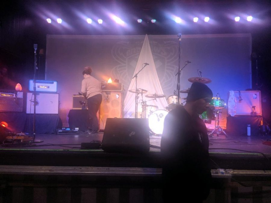 Here, Stage hands are preparing for La Dispute's set. The La Dispute logo can be seen on the bass drum head.