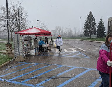 Volunteers work in all types of weather to organize food for pickup. Hundreds of families are served during the event.